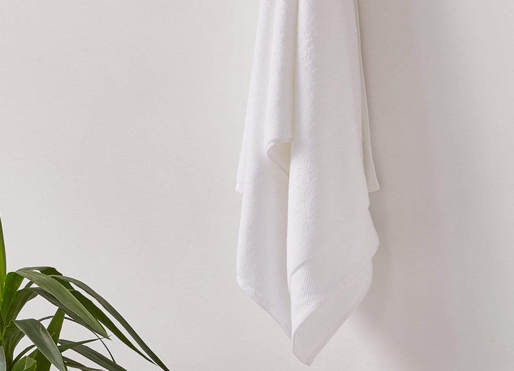 White envello Bath Towel hanging on hook