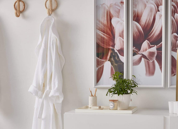 envello Classic Plush Cotton Bathrobe hanging on a bamboo hook with a large picture of pink flowers.