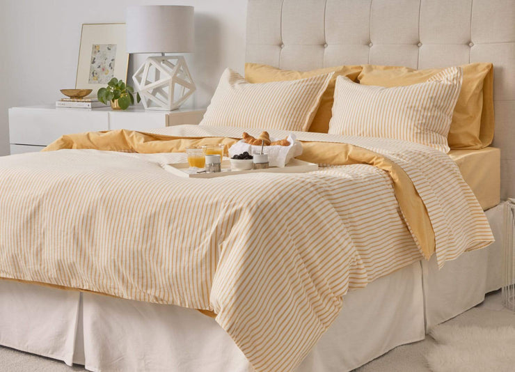 envello Crisp Chambray yellow sheet set on bed with breakfast tray