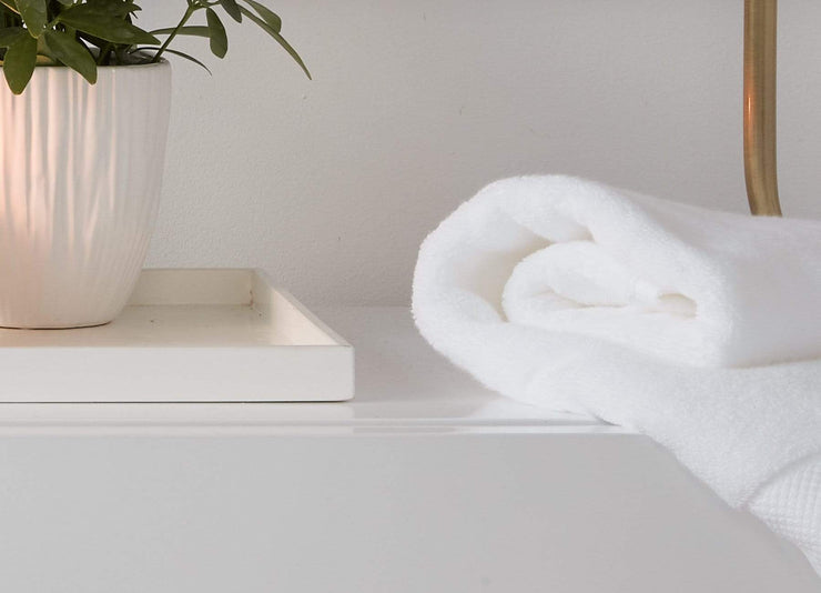 envello white cotton Hand Towel folded and resting on bathroom vanity next to potted plant