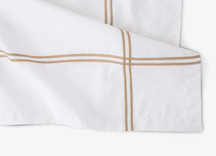 Close-up of envello Select Sateen white cotton duvet set with beige accent trim