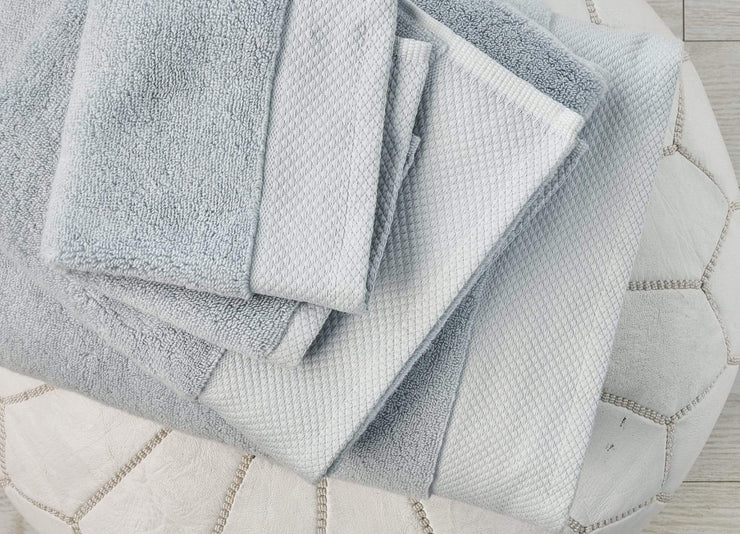 Stacked set of envello light blue cotton Washcloths and Bath Towels on a white leather pouf