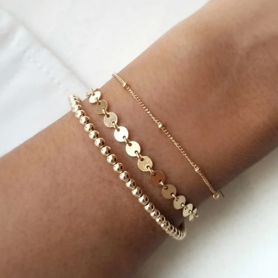 Gold filled chain bracelet paired with two gold bracelets