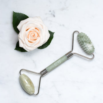 Jade green facial roller beside a white rose