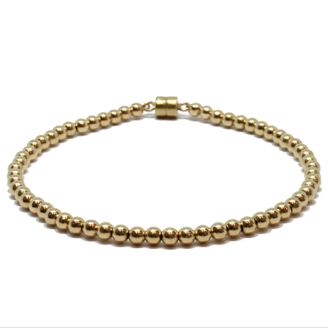 Gold beaded bracelet against white background