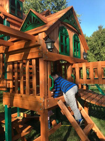 Child climbs into a Gorilla Treasure Trove Treehouse Swing Set assembled by The Assembly Pros