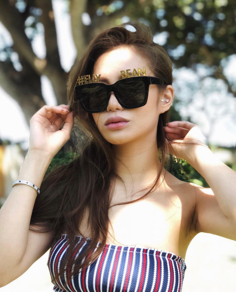 Social media pheomenon Elly Lam 林心兒 wears REVÉ by RENÉ Alphabet Bar Sunglasses and Gold Plated Letters which read 'ELLY BEAN'.