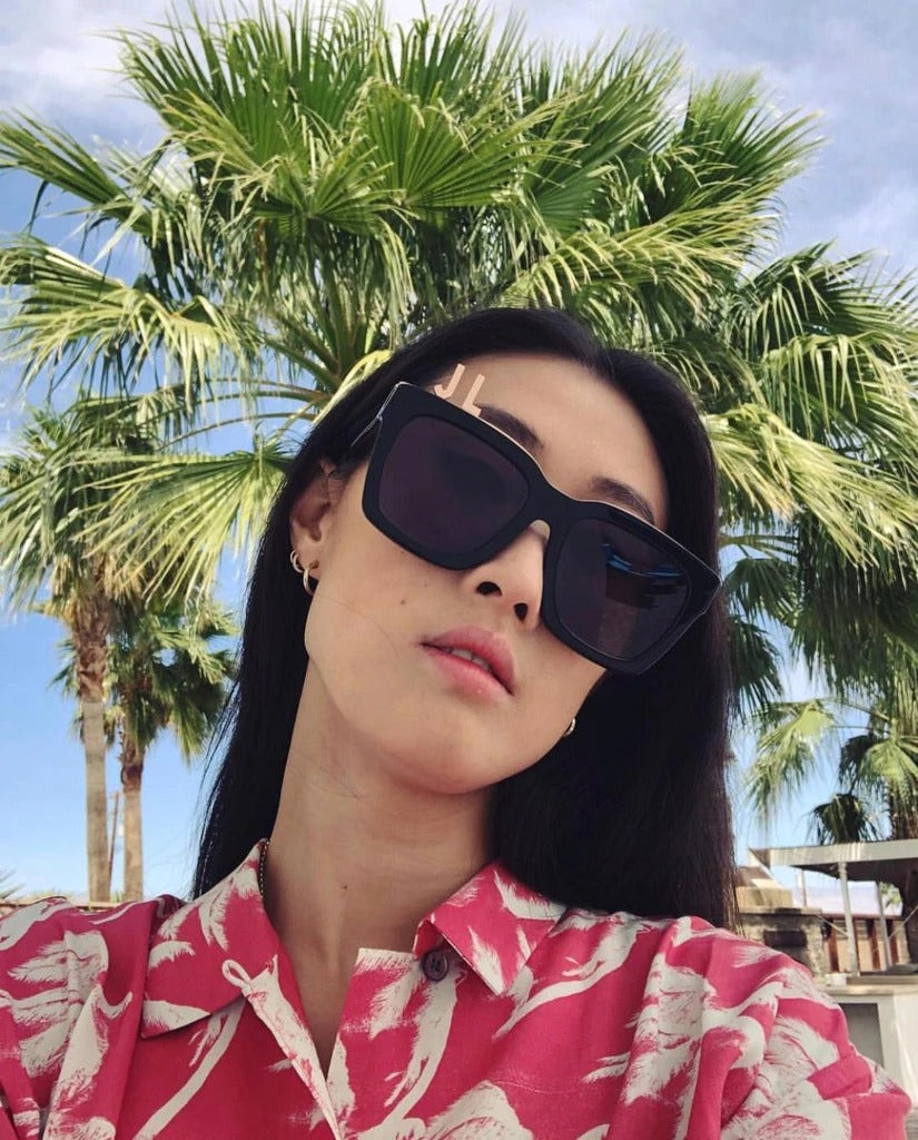 Fashion Director and Stylist Justine Lee  wears REVÉ by RENÉ Alphabet Bar Sunglasses and Gold Plated Letters.