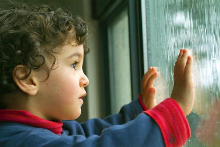 child looking through window on a rainy day