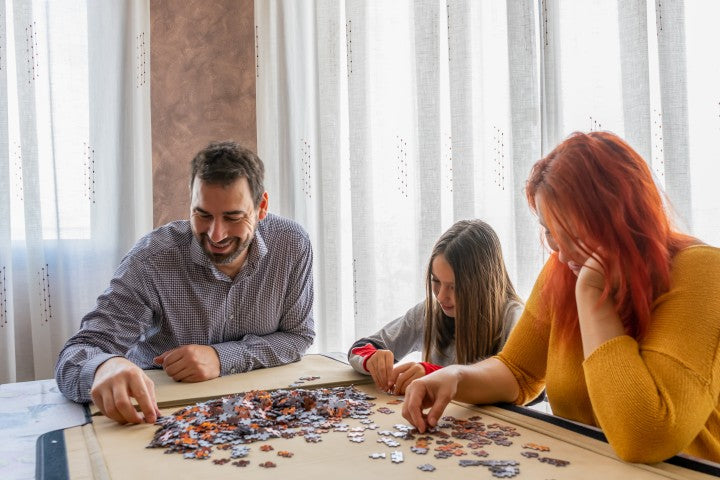 family putting together tabletop puzzle
