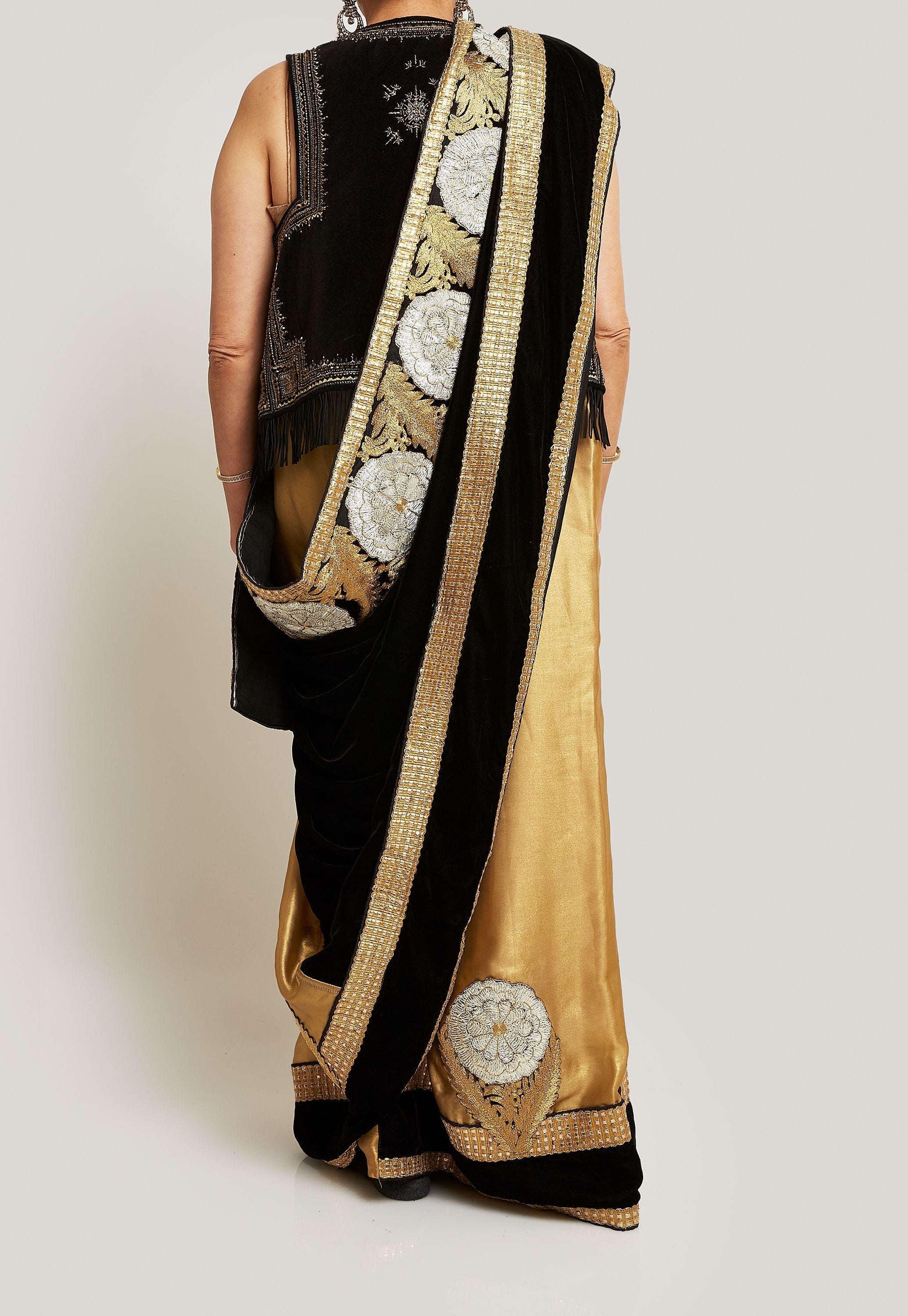 BLACK AND GOLD SILK AND VELVET SAREE WITH PAIRED WITH A GOLD BLOUSE AND A BLACK VELVET AND GOLD EMBELLISHED SLEEVELESS JACKET