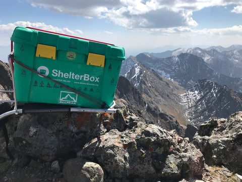 ShelterBox atop 14er with All Peak logo sticker