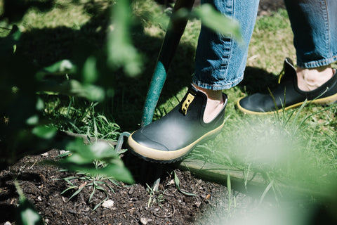 woman digging with a spade wearing Poddy and Black garden shoes