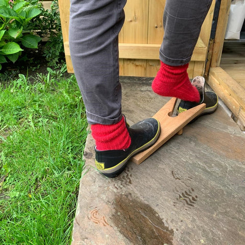 woman taking off her Poddy and Black garden shoes using a boot jack
