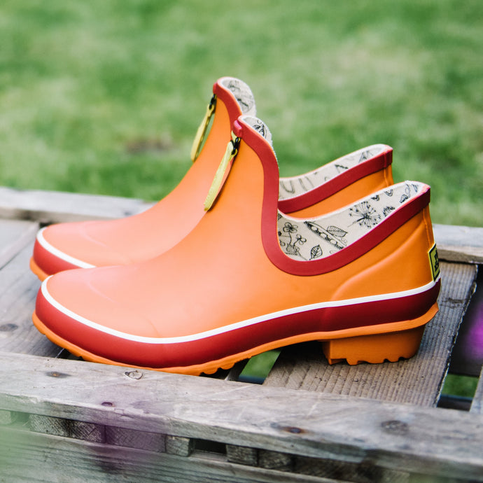 ankle welly in orange on wooden surface