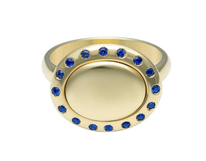 Small oval signet ring with a halo or small sapphires all around edge of face in green 18k gold.