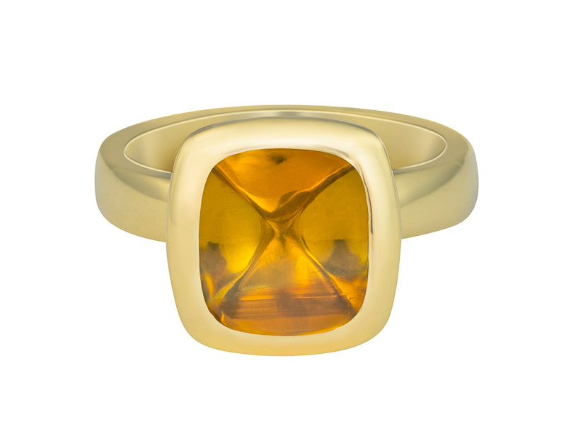 Green gold ring set with upside down medium square cabochon of golden zircon. Gem is set in a frame.