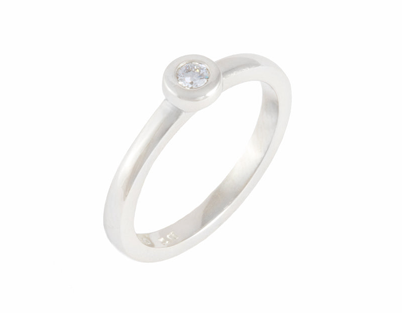 Thin platinum ring set with a round diamond.  The diamond is set in a frame and sits right on top of the band.