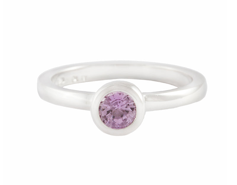 Thin platinum ring set with round pink spinel.  the gem is set in a frame and sits above the band.