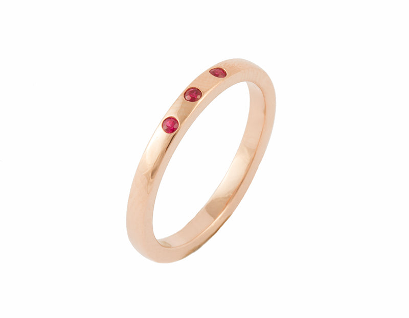 Thin rose gold band set with three bright red round rubies. The gems are set into the band.