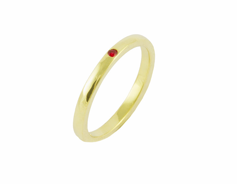 Thin green gold band set with one bright red round ruby. The gems are set into the band.
