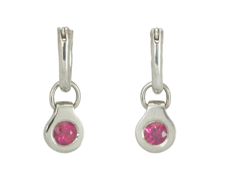 Round drops with rich pink gems in white gold frame. Drops hang on small U shaped hoops in solid white gold.