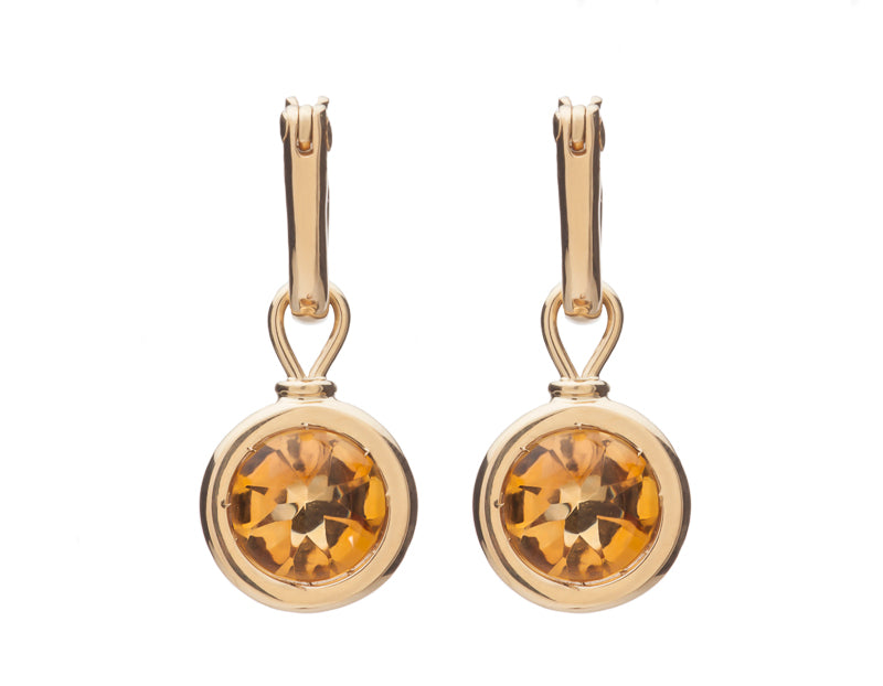 Round drops with bright orange gems in rose gold frame. Drops hang on small U shaped hoops in solid rose gold.