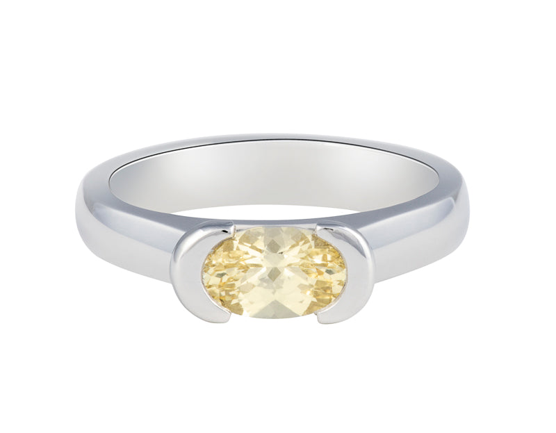 Platinum ring with natural pastel yellow sapphire. The sapphire is oval and lies across the finger and is bezel set at two ends.