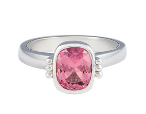 Platinum ring with natural pink spinel.  The gem is rectangular, lies parallel to finger, cut with a checkerboard pattern and surrounded by a frame, that is, bezel set.  Gem setting is raised above the ring.