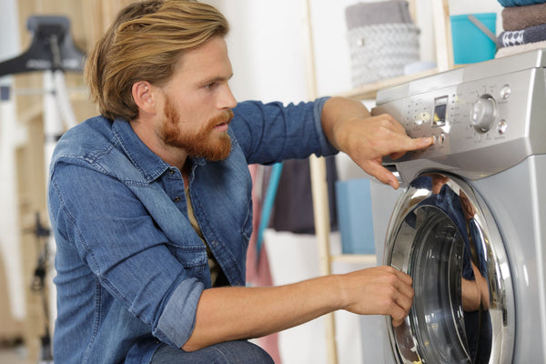 a man putting the washing machine on the lowest cycle setting