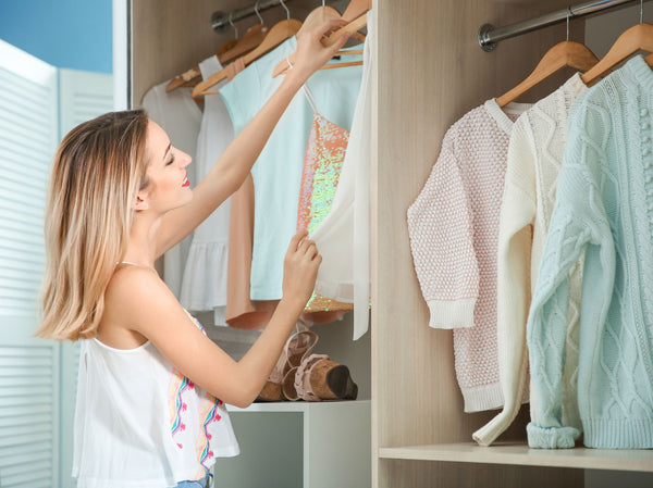 a smiling woman standing in front of her tidy closet