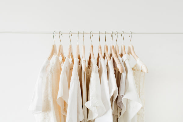 a selection of cream-colored beautiful clothing on a hanging rail