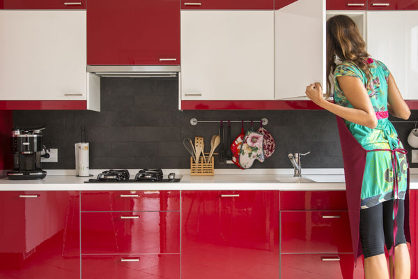 Woman looking into her kitchen cabinets