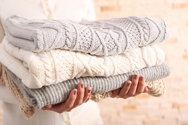 hands holding a neat clean pile of woollens