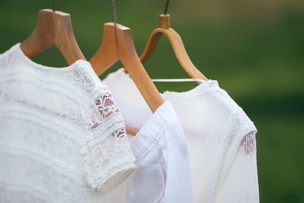some fresh white clothing airing outdoors on wooden hangers