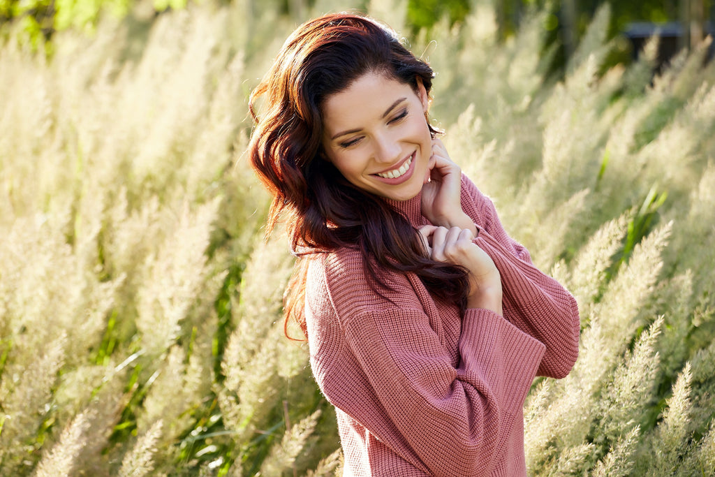 a beautiful woman wearing a dusky pink pullover