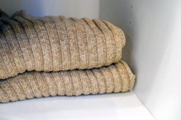 folded ribbed sweaters on a shelf in a white closet