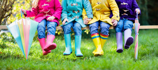 children in brightly colored winter coats and galoshes