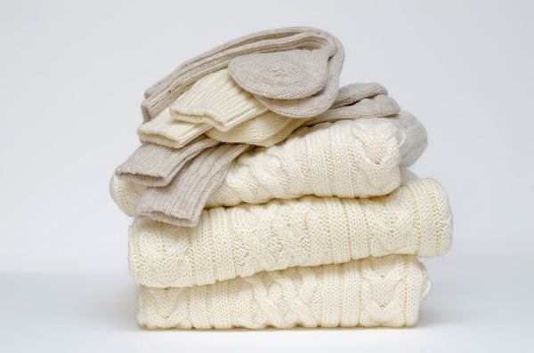 folded pile of  cream woollens with socks on the top of them
