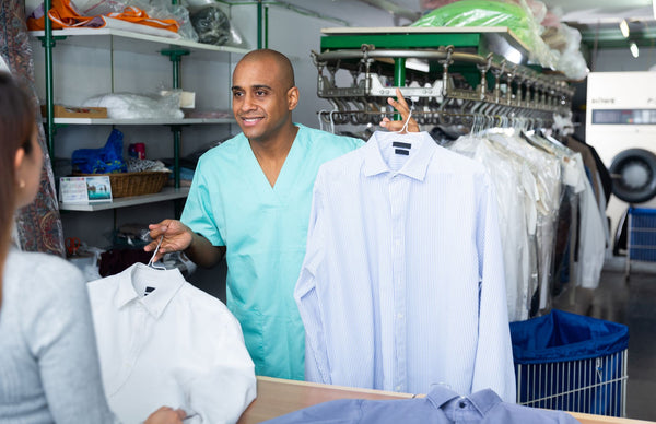 a dry cleaning person handing over some cleaned shirts to a customer