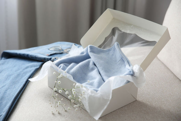 a gift box with a baby blue cashmere sweater inside, with matching denims
