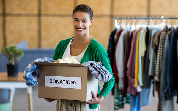 woman holding a donations box full of clothing
