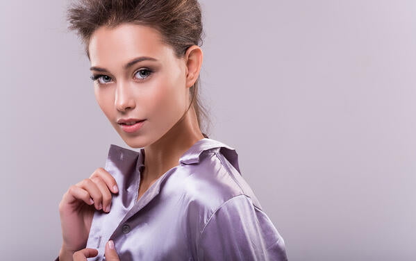 woman touching the fabric of her lilac silk shirt