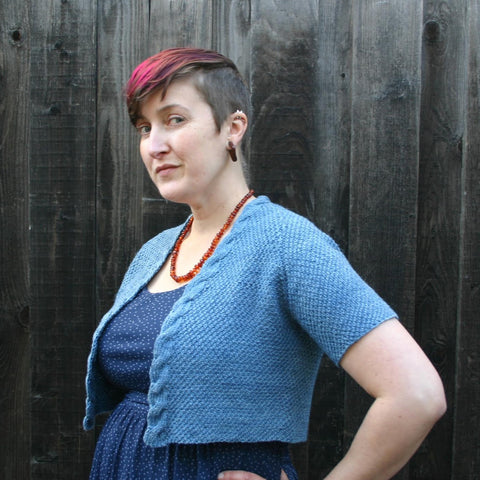 A white woman with close cropped brown hair that is dyed magenta on top is standing in front of a wooden fence.  She is standing at quarter profile with her hand on her hip.  She is wearing a blue dress with a blue, cropped, textured cardigan over it and an amber bead necklace.