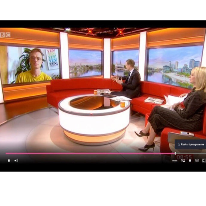 Shot of BBC Breakfast studio with Scott Bryan being interviewed on big screen. He's sitting in front of his colourful YES! art print