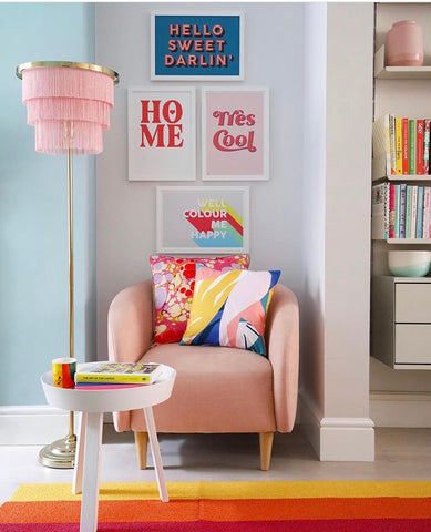 Kin and Castle prints styled by interiors blogger Little Big Bell, Dr Geraldine Tan. Features 4 art prints on the wall in white frames, above a pink armchair. There is also a small white coffee table, and a pink frilly standing lamp.