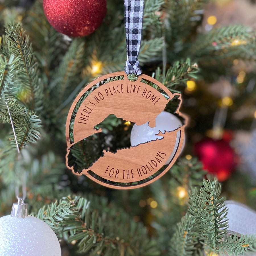 "This is a cherry wood Christmas ornament with a cutout of the map of Nova Scotia; the ornament says ""There's no place like home for the holidays"". In the background you can see the ornament is hung on a Christmas tree with white lights and red and white ornaments."
