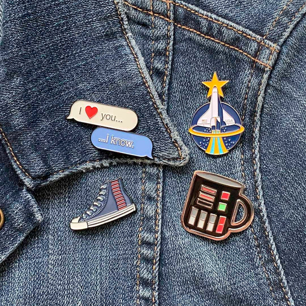 Collectable enamel pins featuring the Space Shuttle, Text message, Run Solo, and Coffee Mug all designed by illustrator Brian Miller for Oktopolis