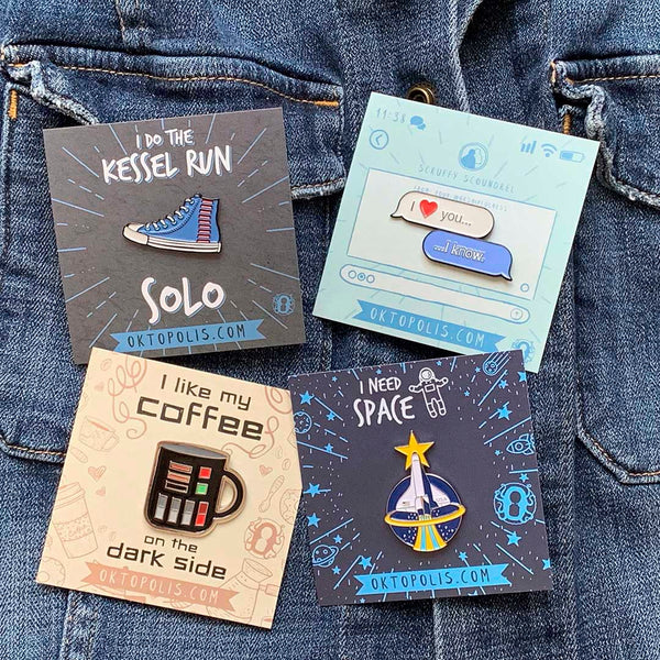 Collectable enamel pins on keepsake card backs featuring the Space Shuttle, Text message, Run Solo, and Coffee Mug all designed by illustrator Brian Miller for Oktopolis