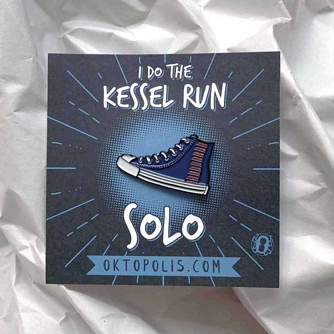 Collectable enamel pin of a running shoe with blood stripes featuring a keepsake display card with the inscription I DO THE KESSEL RUN SOLO designed by illustrator Brian Miller for Oktopolis